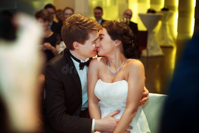 De mooie kussen die van het huwelijkspaar op de laag in een restauran zitten stock afbeeldingen