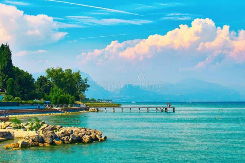 De mooie landschapsmening van de zomermeer Garda in Italië met turkoois water en verbazende roze avond betrekt royalty-vrije stock foto's