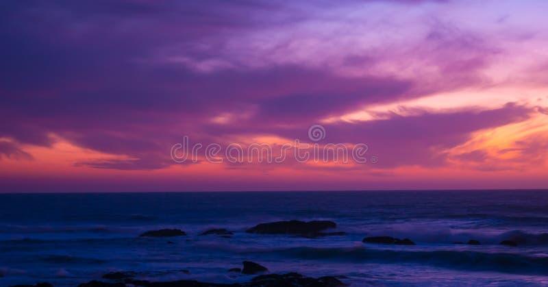 De mooie lange blootstelling schoot over oceaan bij schemer vlak na zonsondergang met rode magenta gradiënthemel stock afbeelding