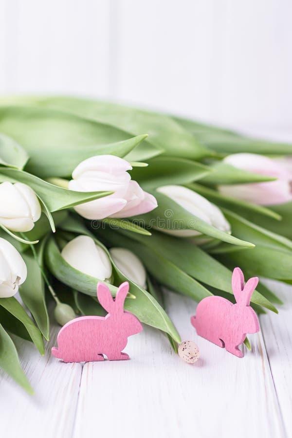 De mooie lente bloeit tulpen en roze Paashazen op een witte achtergrond Vrije ruimte stock afbeeldingen