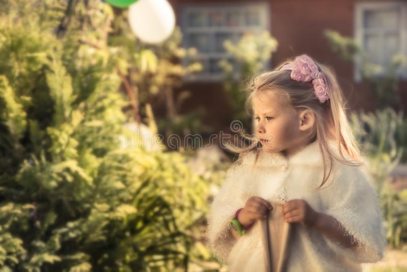 De mooie leuke prinses van het kindmeisje in mantel in openlucht portret met warm van de zonlicht zacht groen formeel tuin concep royalty-vrije stock fotografie