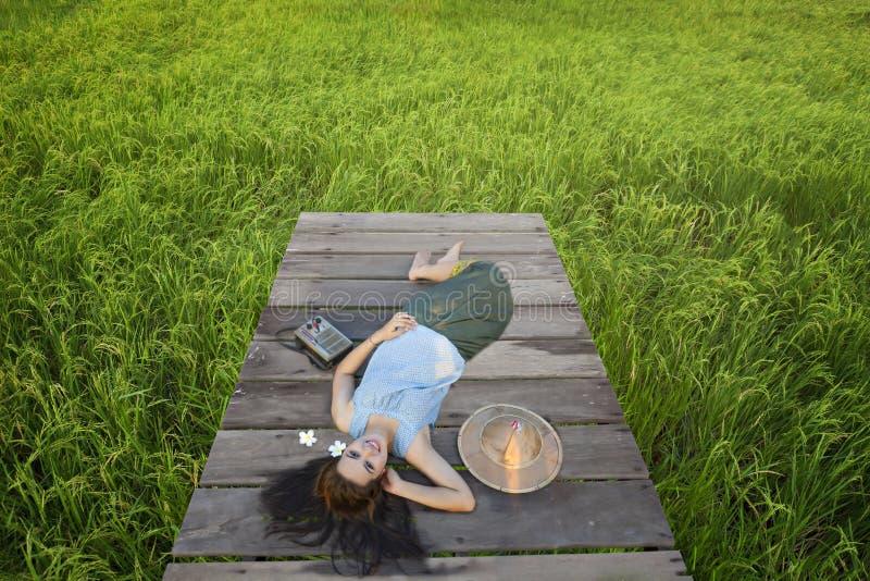 De mooie lokale jonge vrouw die van Thailand op houten brug en het luisteren radio in padieveld liggen stock afbeeldingen