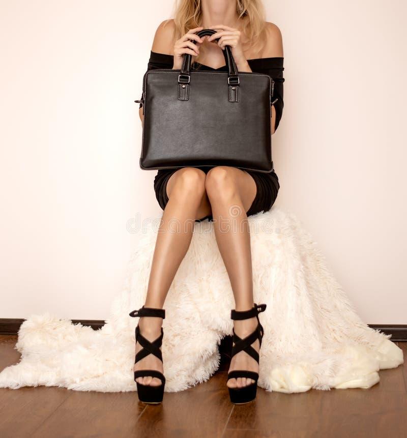 De mooie luxueuze jonge vrouw in een zwarte kleding zit op een witte bontdekking in zwarte modieuze sandals en een handtas royalty-vrije stock foto's