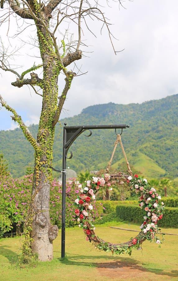 De mooie mandschommeling van het huwelijk verfraaide met de kleurrijke rozenbloem in de aardtuin die op pool onder boom hangen royalty-vrije stock afbeeldingen