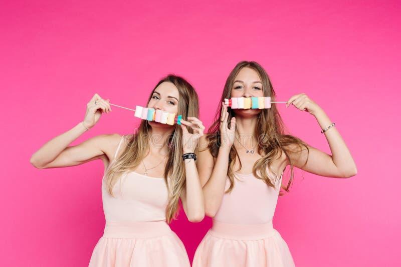 De mooie meisjes houden van poppen die pret met heemstsuikergoed hebben op stok royalty-vrije stock afbeelding