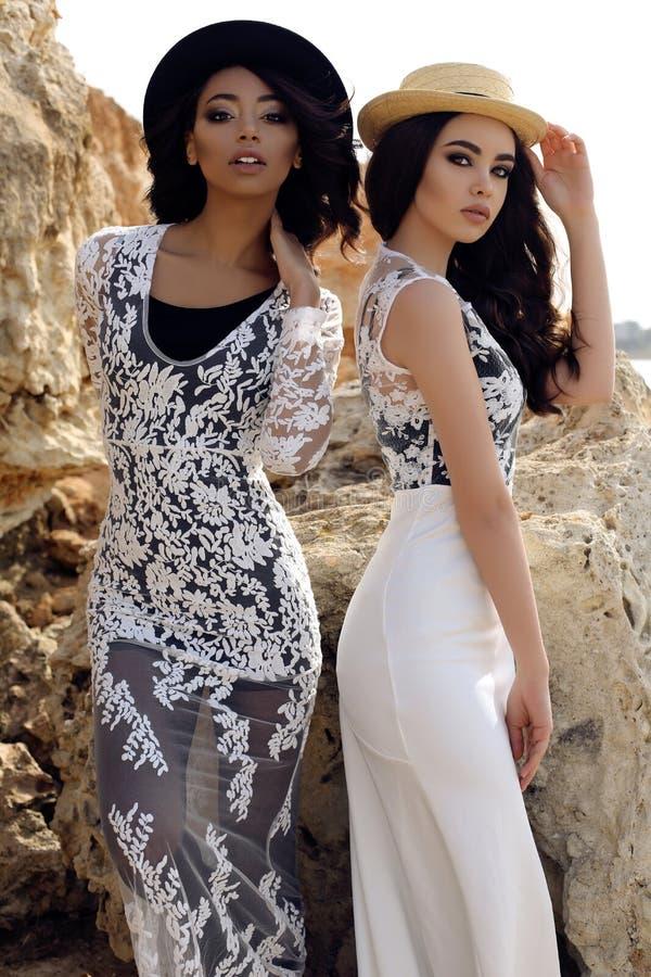 De mooie meisjes met donker haar draagt toevallige elegante kleren en hoed royalty-vrije stock afbeeldingen