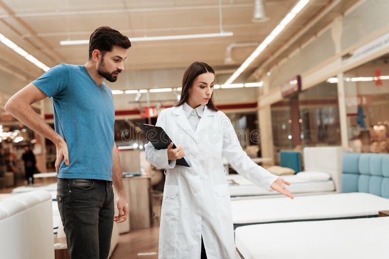 De mooie meisjesadviseur toont orthopedische matras aan de zekere mens in meubilairopslag aan stock foto