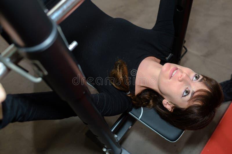 De mooie meisjesbodybuilder voert oefening met gewicht uit royalty-vrije stock fotografie