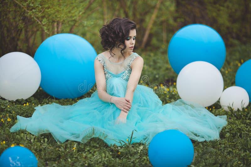 De mooie meisjesgediplomeerde in een blauwe kleding zit op het gras dichtbij grote blauwe en witte ballons Peinzende elegant stock fotografie