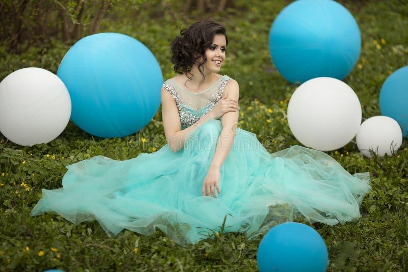 De mooie meisjesgediplomeerde in een blauwe kleding zit op het gras dichtbij grote blauwe en witte ballons Vrolijke elegant royalty-vrije stock afbeeldingen