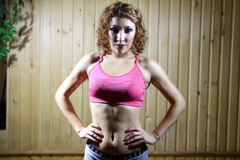 De mooie meisjestribune stelt binnen van bokser in de gymnastiek stock foto