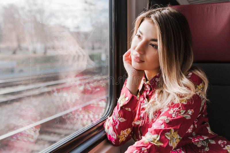 De mooie meisjeszitting alleen in een trein en droevig kijkt uit het venster royalty-vrije stock fotografie