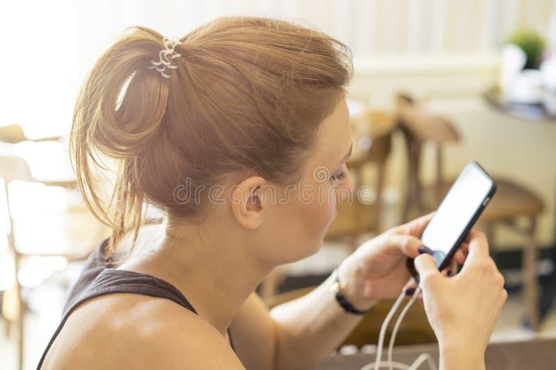 De mooie meisjeszitting bij een lijst met koffie het typen schrijft bericht op smartphone royalty-vrije stock foto