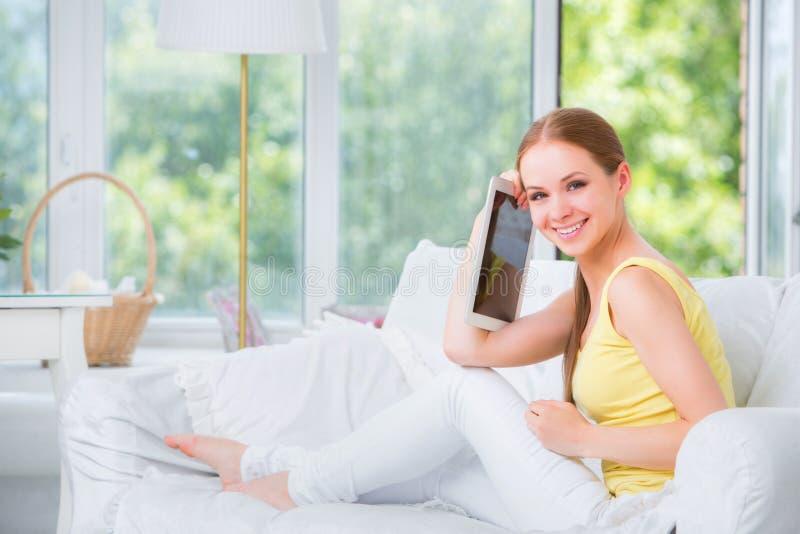 De mooie meisjeszitting op een bank tegen het venster en toont de elektronische tablet royalty-vrije stock fotografie