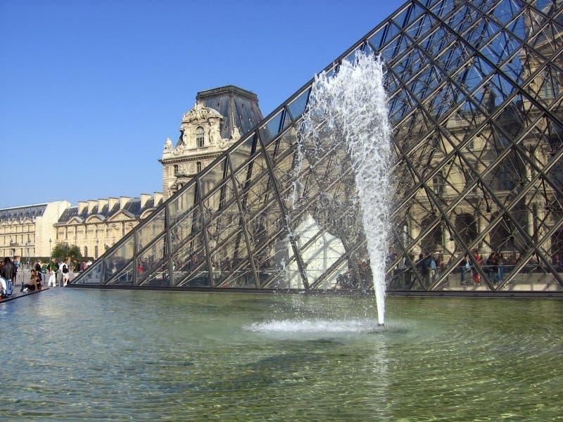 De mooie mening van het Louvremuseum verglaasde piramide en fontein met waterstraal stock foto