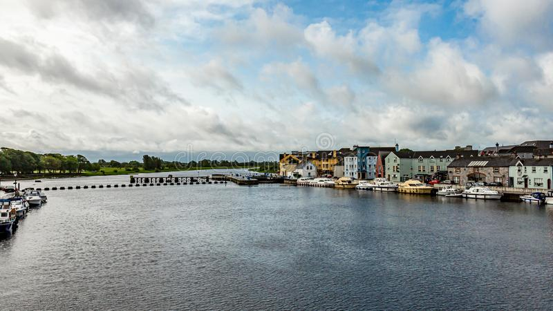 De mooie mening van de rivier Shannon met boten verankerde op de kust en de schilderachtige huizen stock foto's