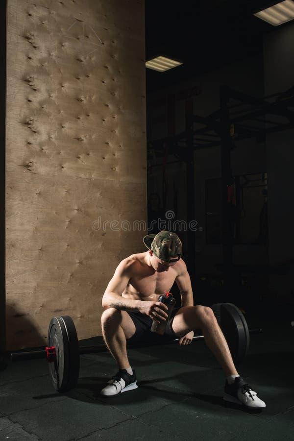 De mooie mens vermoeide na gewichtheffen bij gymnastiek stock foto's