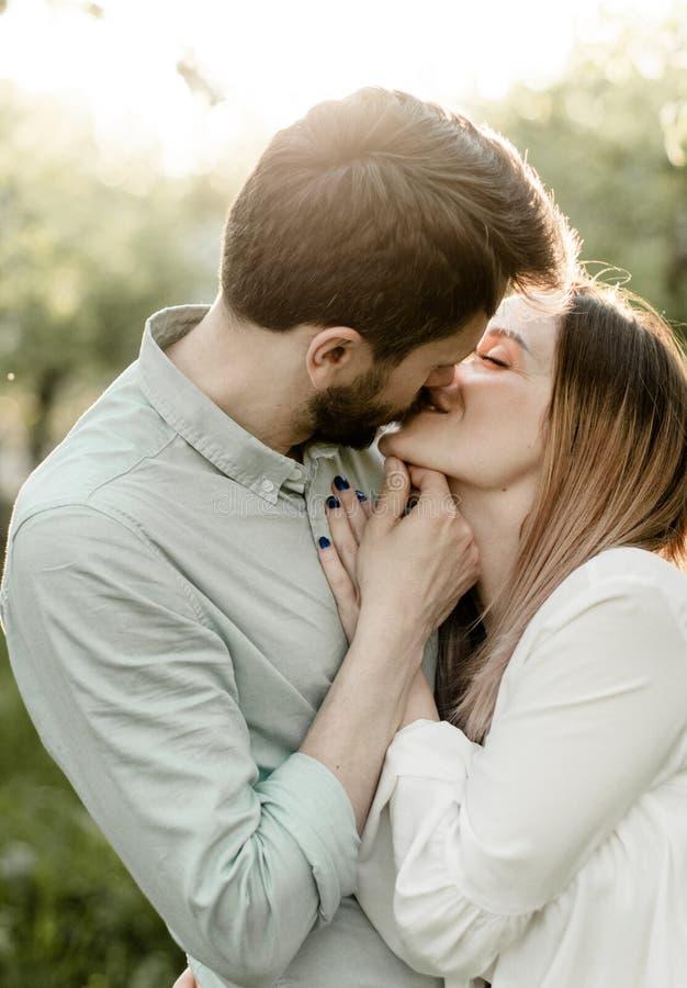 De mooie minnaars kussen in de bloeiende tuin stock foto's