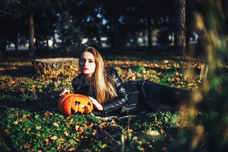 De mooie moderne pompoen van Halloween van de heksenholding in bosoktober Gelukkige Vakantie stock fotografie