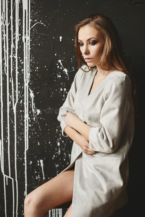 De mooie modieuze half-naked bruin-haired vrouw in zit voor donkere achtergrond stock foto's