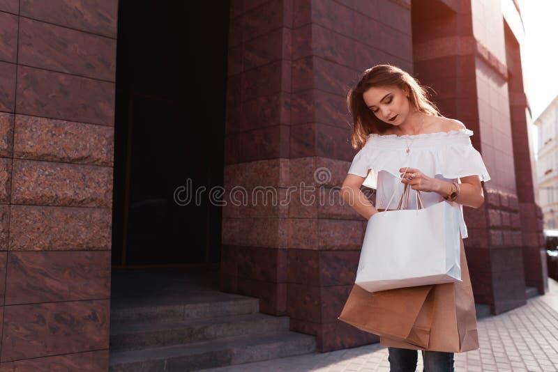 De mooie modieuze jonge vrouw die met het winkelen zakken van wandelgalerij opstappen en ontvangt een vraag Bezige vrouw in zeven royalty-vrije stock afbeeldingen