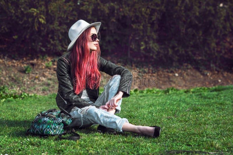 De mooie modieuze rode haired zitting van de manier hipster modelvrouw in openlucht op groen gras bij park die zonnebril, hoed en royalty-vrije stock afbeeldingen
