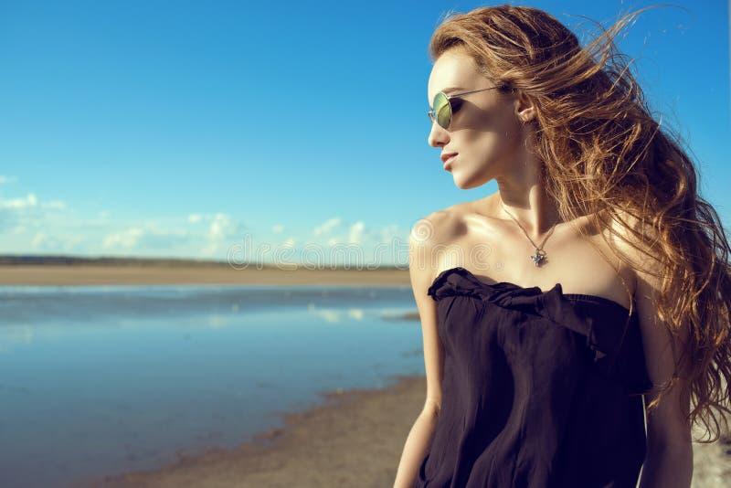De mooie modieuze vrouw met de wind in haar haar die zwarte open schouder hoogste en in ronde dragen weerspiegelde zonnebril bij  stock afbeelding