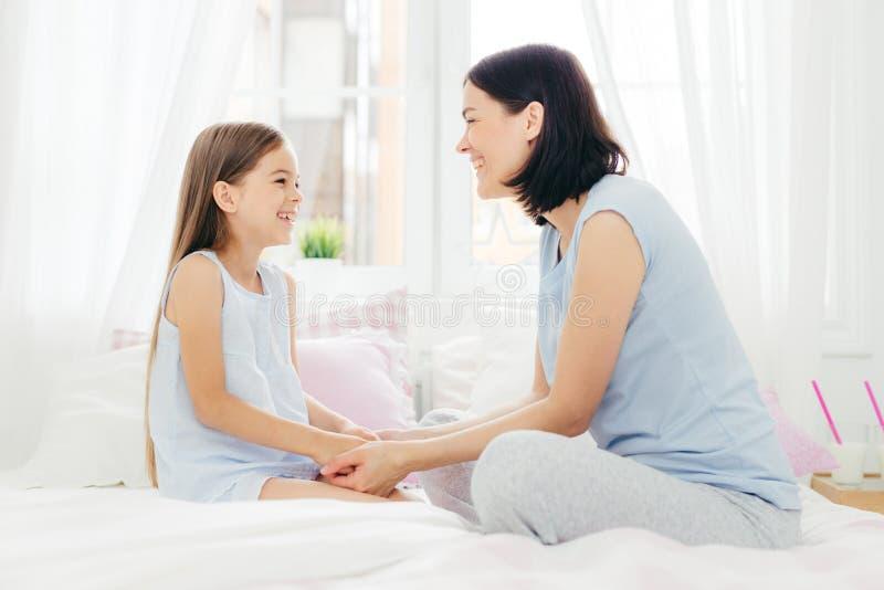 De mooie moeder en de dochter genieten van samenhorigheid, samenhouden hand, hebben prettige bespreking, zitten op comfortabel be royalty-vrije stock foto