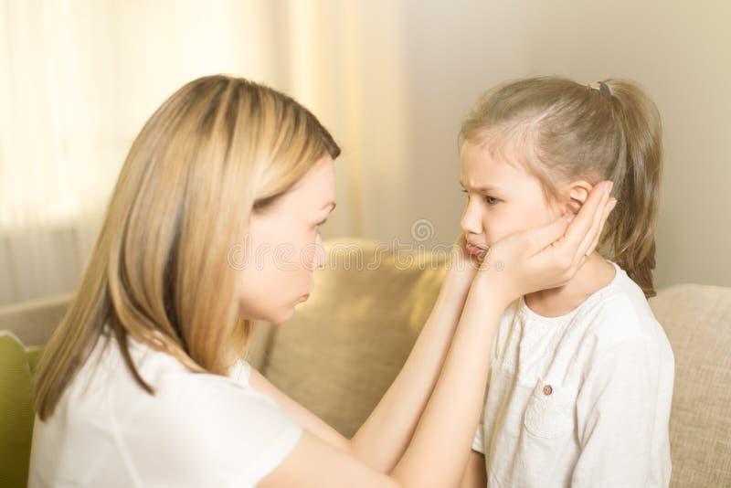 De mooie moeder troost zijn jonge gefrustreerde dochter royalty-vrije stock afbeelding