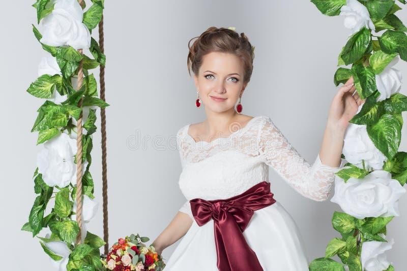 De mooie mooie bruid zit op een schommeling met een mooi boeket van kleurrijke bloemen in een witte kleding met avondkapsel stock foto's