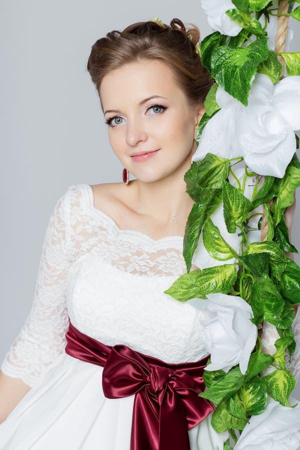 De mooie mooie bruid zit op een schommeling met een mooi boeket van kleurrijke bloemen in een witte kleding met avondkapsel royalty-vrije stock fotografie