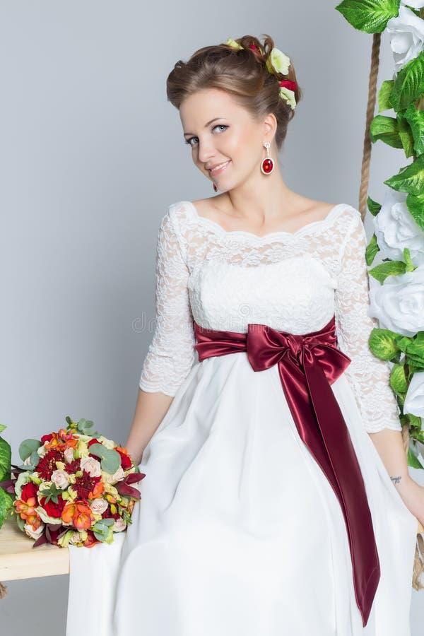 De mooie mooie bruid zit op een schommeling met een mooi boeket van kleurrijke bloemen in een witte kleding met avondkapsel stock fotografie