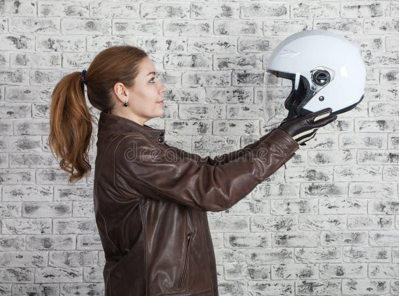 De mooie motorrijder selecteert witte open helm terwijl het houden in het uitrekken van wapens, bakstenen muurachtergrond, zijaan royalty-vrije stock foto