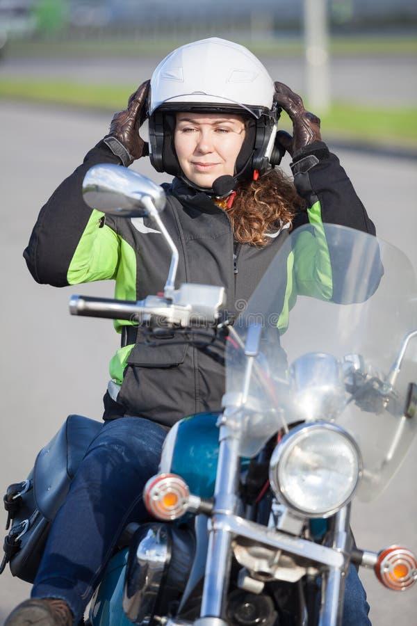 De mooie motorrijdervrouw dirkt op zich terwijl het zitten op fiets en het bekijken achterspiegel royalty-vrije stock afbeeldingen
