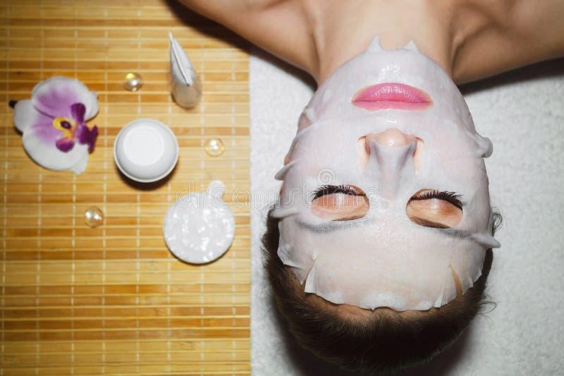De mooie natuurlijke meisjesvrouw in de kuuroordsalon, het maakt een gezichtsmasker royalty-vrije stock afbeelding