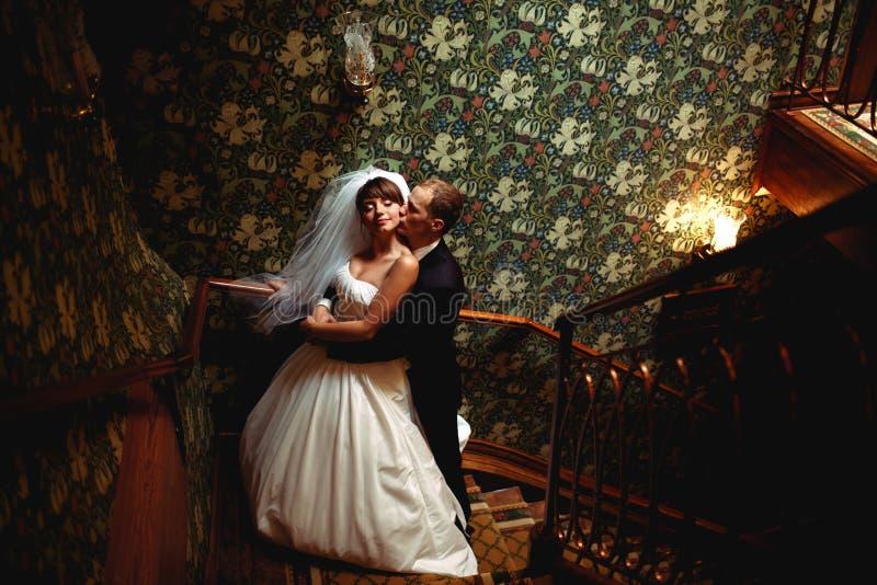 De mooie omhelzingen van het huwelijkspaar op de oude treden in een houten zaal royalty-vrije stock foto's