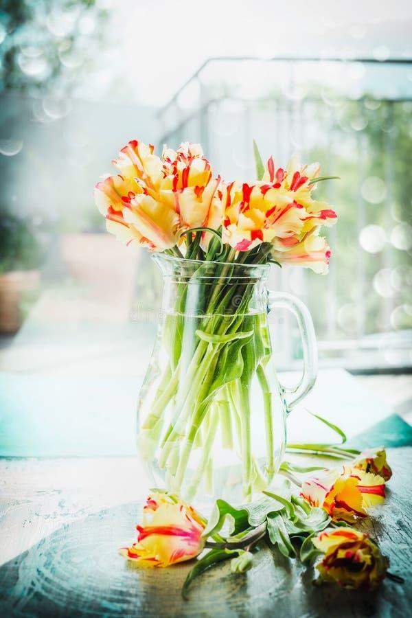 De mooie ongebruikelijke gevlekte rode en gele tulpen bundelen in glasvaas bij venster met de lenteaard Papegaaitulpen stock foto