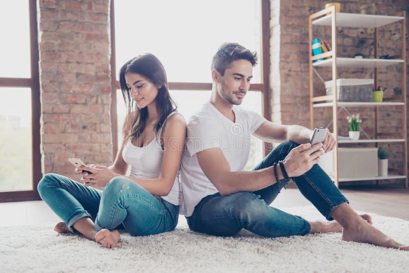 De mooie ontspannen broer en de zuster doorbladeren op hun telefoon stock afbeelding