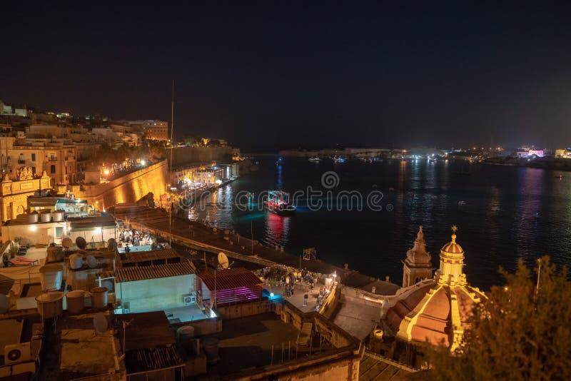 De mooie oude stad van Valletta bij nacht met vele mensen overvol door levend te letten op kustlijn toont en op het vuurwerk te w stock afbeeldingen