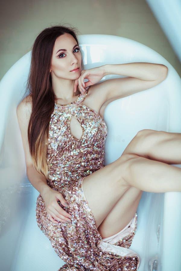 De mooie overweldigende jonge vrouw in het verbazen schittert lovertjeskleding ligt in een wit bad De heldere volledige lippen, h stock fotografie