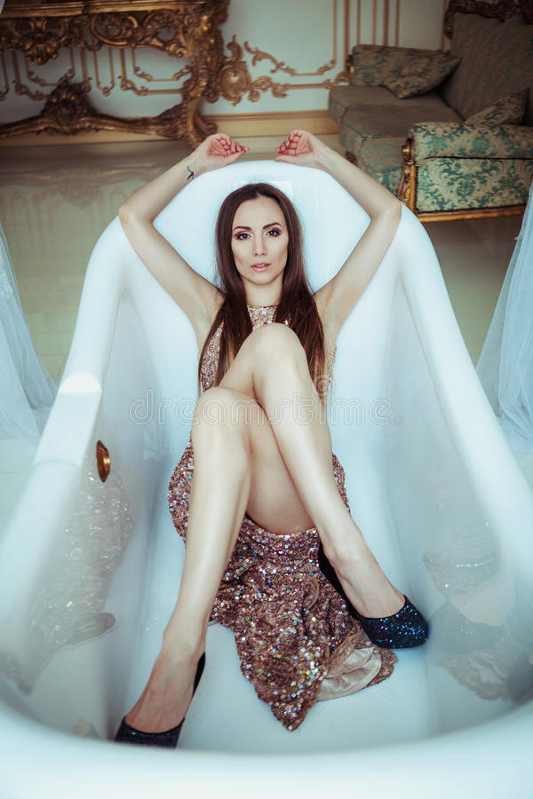 De mooie overweldigende jonge vrouw in het verbazen schittert lovertjeskleding ligt in een wit bad De heldere volledige lippen, h royalty-vrije stock foto's