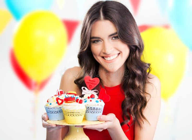De mooie partij van de vrouwenholding cupcakes royalty-vrije stock afbeeldingen