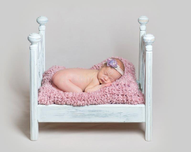 De mooie pasgeboren slaap van het babymeisje op de voederbak royalty-vrije stock foto's