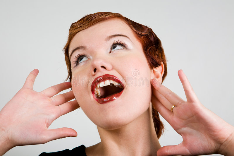 De mooie red-head jonge vrouw met verrast kijkt stock foto's