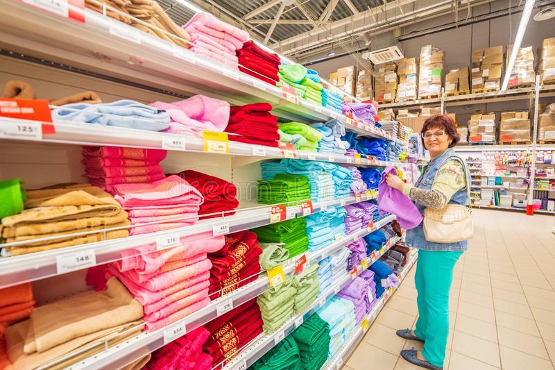 De mooie rijpe vrouw in een denimkostuum kiest handdoeken voor het toilet stock foto's