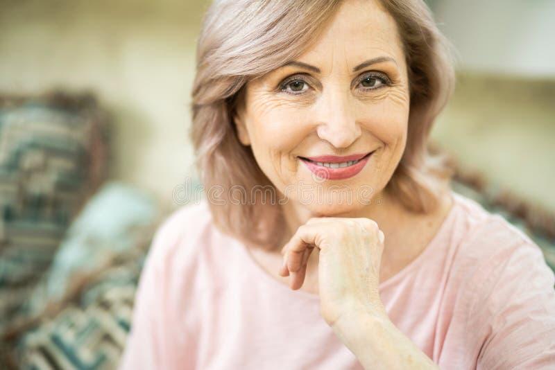 De mooie rijpe vrouw glimlacht zacht bij camera royalty-vrije stock afbeeldingen
