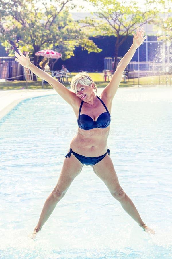 De mooie rijpe vrouw in zwempak maakt gymnastiek royalty-vrije stock afbeelding
