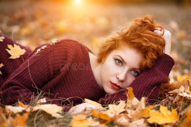 De mooie rode haired vrouw in de herfstpark ligt in gevallen gebladerte op een Zonnige dag, het licht stock afbeeldingen