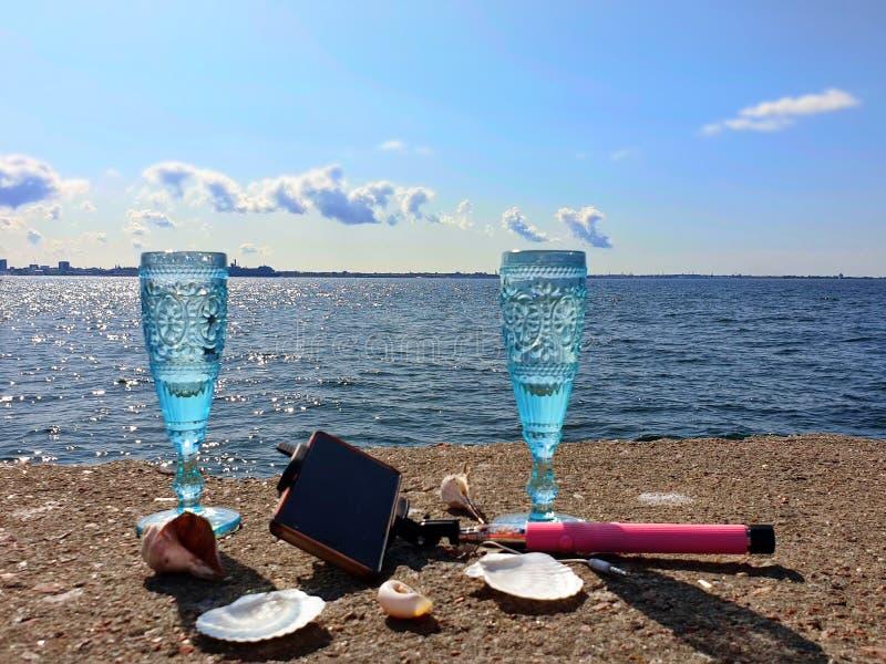 De mooie romantische zomer van de aardvakantie bij zonsondergangzeegezicht twee blauwe glazen van Champagne-het leven wildernis v royalty-vrije stock foto's
