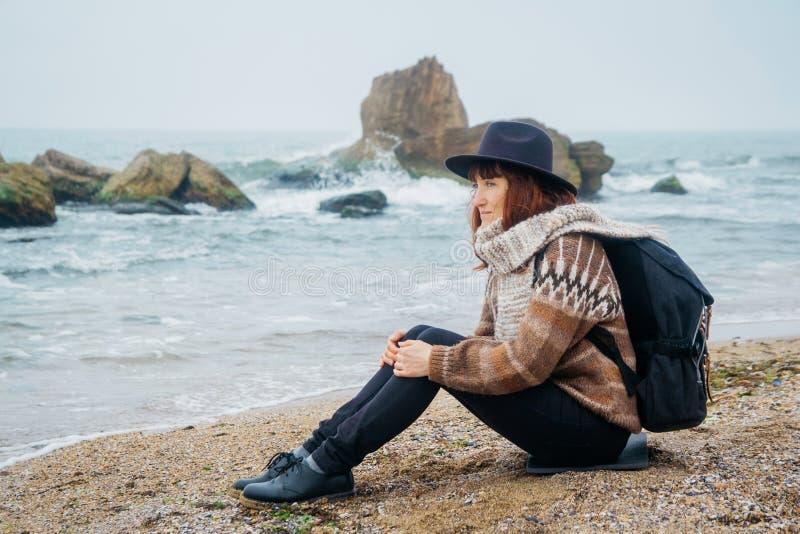 De mooie roodharige vrouw in een hoed en een sjaal met een rugzak zit op de kust tegen de achtergrond van de rotsen royalty-vrije stock afbeelding